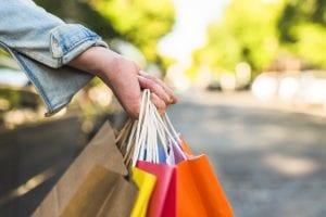 moters ranka su prekių maišais